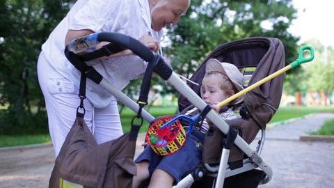 Naughty boy in the buggy with granny Stock Video Footage