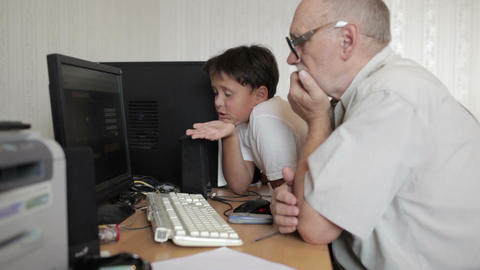 Grandfather repairs grandson computer 1 Stock Video Footage