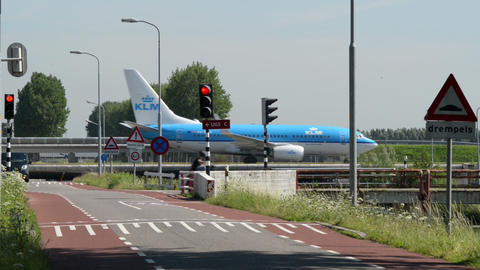 airplane on taxiway and street traffic 11030 Stock Video Footage
