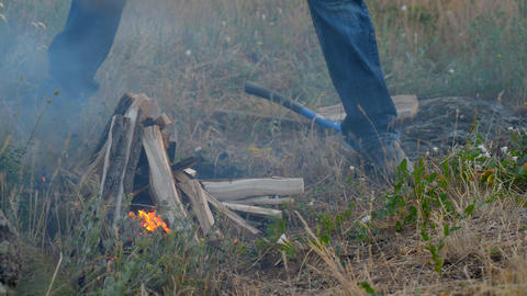 A man lights the fire, the fire on the nature Stock Video Footage