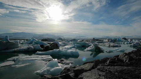 Icebergs melt in the sun in a vast blue glacier la Footage