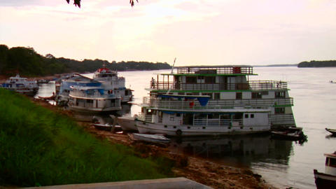 River boats line the waterway on the Amazon River Stock Video Footage
