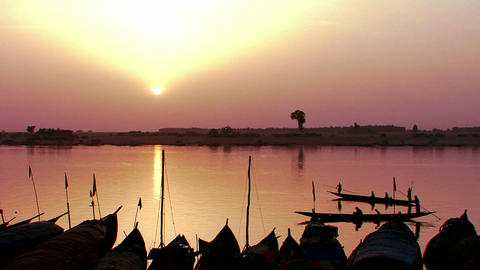 Fishermen row at sunset on the Niger River in beau Stock Video Footage