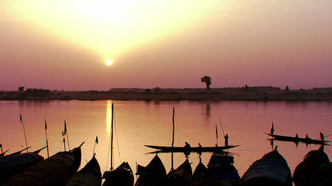 Fishermen row at sunset on the Niger River in beau Footage