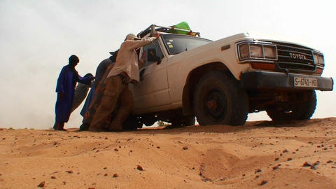 A UN type jeep gets stuck in the sand on a road in Stock Video Footage