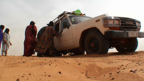 A UN type jeep gets stuck in the sand on a road in Footage