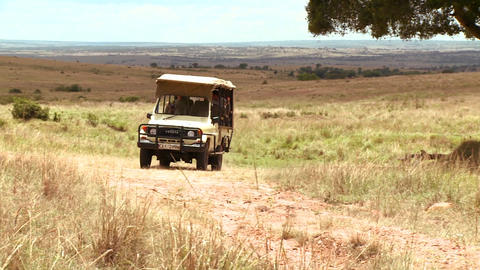 A safari vehicle travels across the plains of Afri Footage