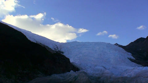 A large glacier spills over a cliff Footage
