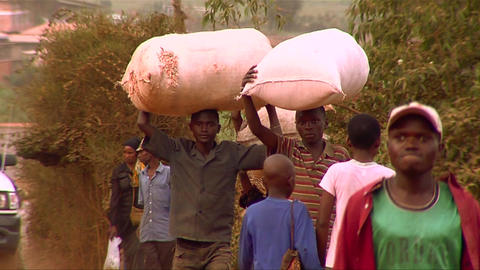 People carry goods on their heads in an African vi Stock Video Footage