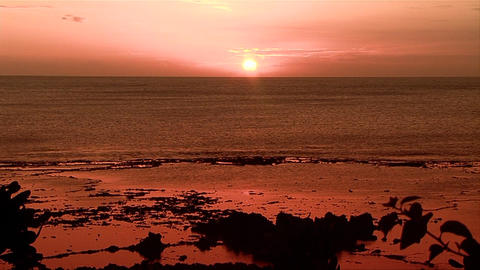 A beautiful red and orange sunset behind the ocean Footage