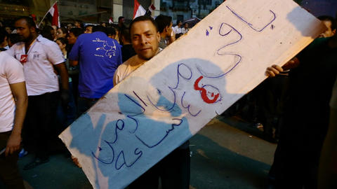 A man carries a homemade sign at a large protest i Stock Video Footage