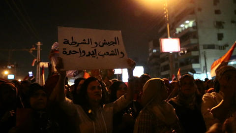 Demonstrators chant at a nighttime rally in Tahrir Stock Video Footage