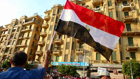 The sun shines through a protestor's flag in Cairo Footage