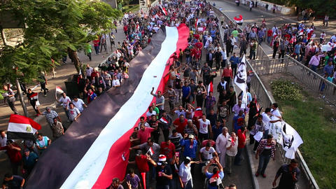 Protestors march and carry a large flag in Cairo, Stock Video Footage