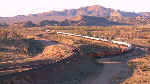 A freight train moves across the desert from a hig Footage