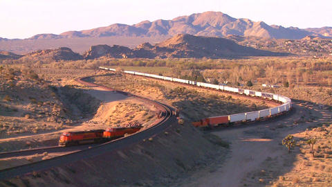 A freight train moves across the desert from a hig Stock Video Footage