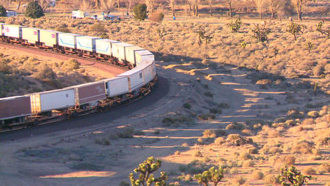 A container freight train moves across the desert Stock Video Footage