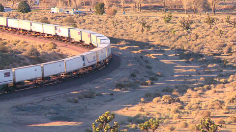 A container freight train moves across the desert  Footage