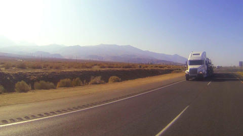 A car carrier truck moves across the desert in thi Stock Video Footage