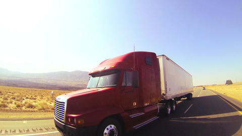 An 18 wheeler truck moves across the desert in thi Footage