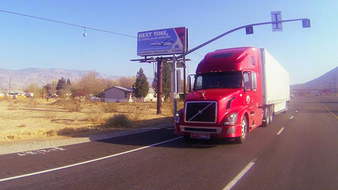 A red 18 wheeler truck moves across the desert in  Footage