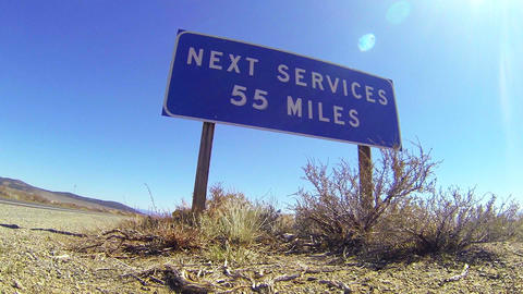 A sign on a lonely desert road warns that the next Footage