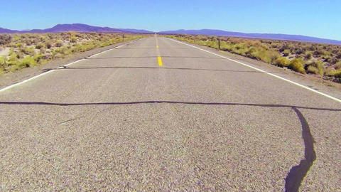 POV shot along a desert road driving fast Footage