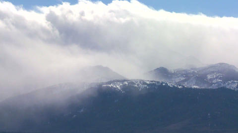 Clouds blow over the top of an alpine mountain ran Stock Video Footage