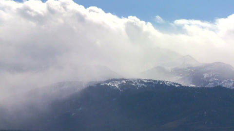 Clouds blow over the top of an alpine mountain ran Footage