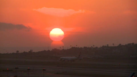 A plane arrives at an airport at sunset or sunrise Footage