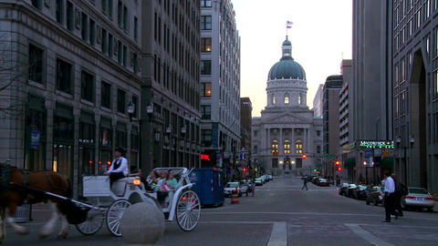 A horse drawn carriage passes the downtown capital Footage