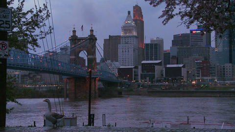 Nighttime falls over Cincinnati as riverboats pass Footage