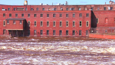 A flooding river flows past an old factory Footage