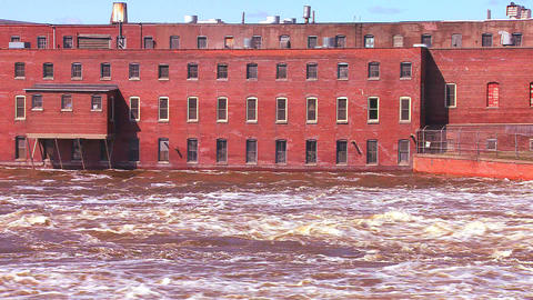 A flooding river flows past an old factory Stock Video Footage