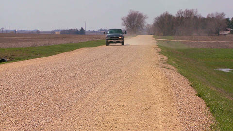 A pickup truck drives on a dirt road through Midwe Footage