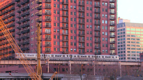 The El train travels over a bridge in front of the Footage