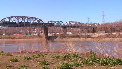 A freight train crosses a bridge over the Missouri Stock Video Footage