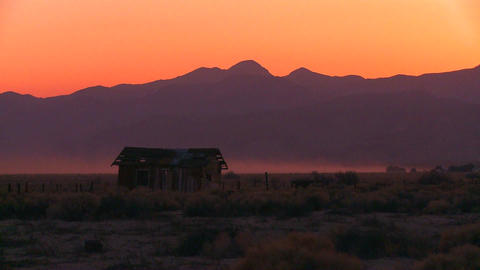 The sun sets behind an abandoned cabin the desert Footage