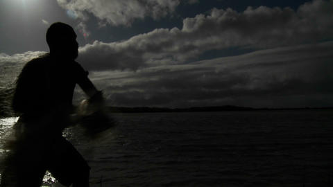 A native fisherman throws his net into the ocean t Stock Video Footage