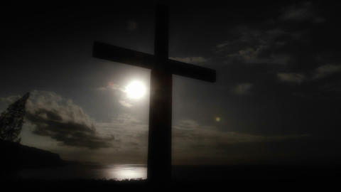 Pan across to a Christian cross against the sun on Footage