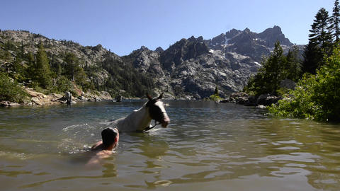 A man taking his horse for a swim in Upper Sardine Stock Video Footage