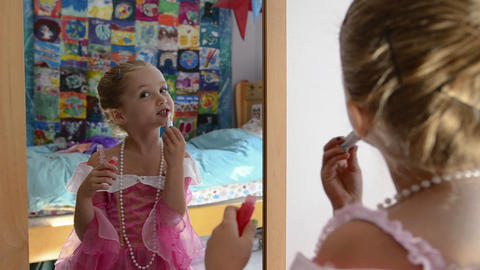 A young girl applying lip gloss while playing dres Stock Video Footage