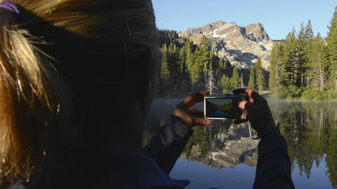 A women taking a photo of a morning reflection of  Footage