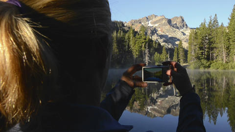 A women taking a photo of a morning reflection of Stock Video Footage