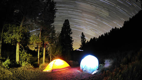 Time lapse star trail streaks over two lite tents  Footage