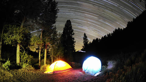 Time lapse star trail streaks over two lite tents Stock Video Footage