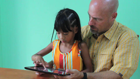 Father And Daughter Playing Game On Digital Tablet Stock Video Footage
