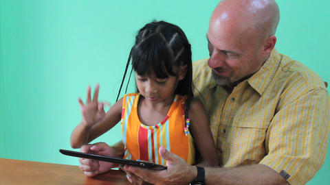 Father And Daughter Playing Game On Digital Tablet Footage