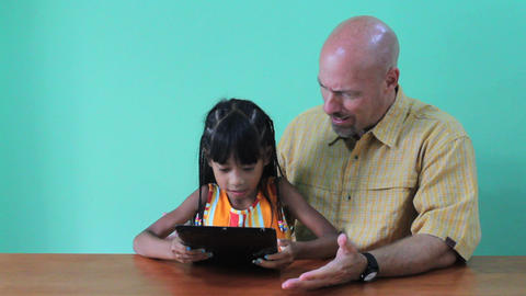 Girl Takes Over Digital Tablet From Dad Stock Video Footage
