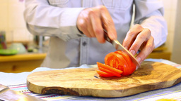 The man cut the tomatoes in the kitchen Stock Video Footage